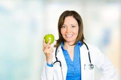 Doctor de sexo femenino sonriente feliz con la manzana verde que se coloca en hospital Imagen de archivo
