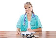 Doctor de sexo femenino sonriente hermoso en la tabla que mira el aislador de la cámara Foto de archivo