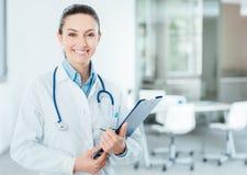 Doctor de sexo femenino sonriente que lleva a cabo informes médicos foto de archivo