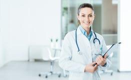 Doctor de sexo femenino sonriente que lleva a cabo informes médicos