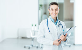 Doctor de sexo femenino sonriente que lleva a cabo informes médicos Foto de archivo libre de regalías