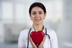 Doctor de sexo femenino sonriente que sostiene el corazón rojo y un estetoscopio imagenes de archivo