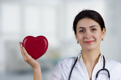 Doctor de sexo femenino sonriente que sostiene el corazón rojo y un estetoscopio fotografía de archivo libre de regalías