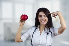 Doctor de sexo femenino sonriente que sostiene la manzana roja imágenes de archivo libres de regalías