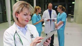 Doctor de sexo femenino sonriente que usa la tableta digital en pasillo del hospital metrajes