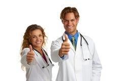 Doctor de sexo femenino y de sexo masculino atractivo que da la aprobación fotografía de archivo