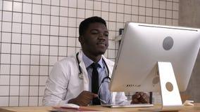 Doctor de sexo masculino africano que tiene videoconferencia en su ordenador almacen de video