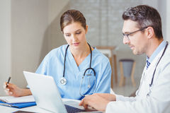 Doctor de sexo masculino con el colega que trabaja en el ordenador portátil Foto de archivo