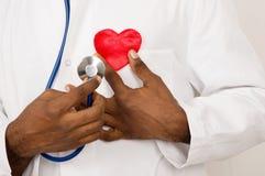 Doctor de sexo masculino con el estetoscopio que lleva a cabo el corazón foto de archivo