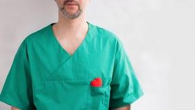Doctor de sexo masculino con la barba en traje verde con el corazón rojo brillante en bolsillo del pecho en el fondo blanco vacío fotografía de archivo