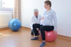 Doctor de sexo masculino con la mujer embarazada que se sienta en bola de la aptitud Fotografía de archivo