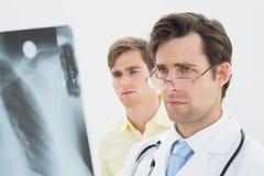 Doctor de sexo masculino concentrado y radiografía de examen paciente de los pulmones Foto de archivo libre de regalías