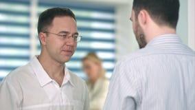 Doctor de sexo masculino confiado que habla con el paciente masculino almacen de video