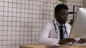 Doctor de sexo masculino del africano que entra que se sienta en el escritorio y el trabajo del comienzo metrajes