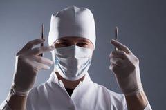 Doctor de sexo masculino en el casquillo, la máscara y los guantes médicos de goma sosteniendo el cuero cabelludo Imágenes de archivo libres de regalías