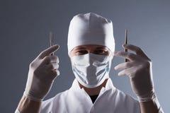 Doctor de sexo masculino en el casquillo, la máscara y los guantes médicos de goma sosteniendo el cuero cabelludo Foto de archivo libre de regalías