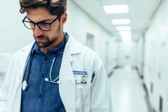 Doctor de sexo masculino en pasillo del hospital Foto de archivo libre de regalías