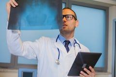 Doctor de sexo masculino en uniforme con la tableta que mira la radiografía Fotos de archivo libres de regalías