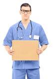 Doctor de sexo masculino gruñón que lleva a cabo una muestra de la historieta Fotografía de archivo libre de regalías