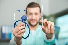 Doctor de sexo masculino joven confiado con el estetoscopio que sostiene la jeringuilla Imágenes de archivo libres de regalías