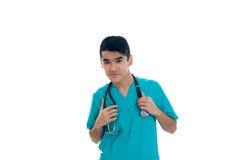 Doctor de sexo masculino joven hermoso con el estetoscopio en la presentación del uniforme aislado en el fondo blanco Foto de archivo