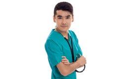 Doctor de sexo masculino joven hermoso con el estetoscopio en la presentación del uniforme aislado en el fondo blanco Foto de archivo libre de regalías