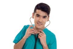 Doctor de sexo masculino joven hermoso en el uniforme con la presentación del stathoscope aislado en el fondo blanco Foto de archivo libre de regalías