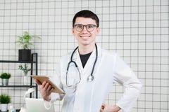 Doctor de sexo masculino joven hermoso sonriente usando la tableta Tecnologías en concepto de la medicina fotos de archivo