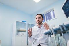 Doctor de sexo masculino joven que explica la exploración del ultrasonido a la mujer embarazada en hospital Foto de archivo libre de regalías
