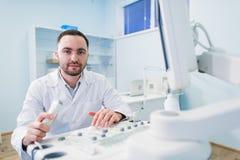 Doctor de sexo masculino joven que explica la exploración del ultrasonido a la mujer embarazada en hospital Fotografía de archivo libre de regalías
