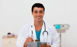 Doctor de sexo masculino joven que lleva a cabo una tarjeta de clip Imágenes de archivo libres de regalías