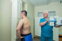 Doctor de sexo masculino maduro paciente del mediados de hombre adulto que pone la máquina para tomar la radiografía Foto de archivo
