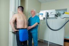 Doctor de sexo masculino maduro paciente del mediados de hombre adulto que pone la máquina para tomar la radiografía Foto de archivo libre de regalías