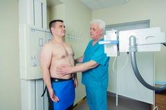 Doctor de sexo masculino maduro paciente del mediados de hombre adulto que pone la máquina para tomar la radiografía Imagen de archivo libre de regalías