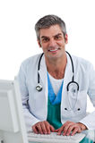 Doctor de sexo masculino maduro que trabaja en un ordenador Foto de archivo