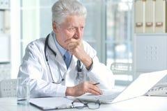 Doctor de sexo masculino mayor confiado con el estetoscopio que trabaja en oficina Fotografía de archivo