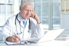 Doctor de sexo masculino mayor confiado con el estetoscopio que trabaja en oficina Fotografía de archivo libre de regalías