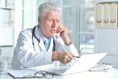 Doctor de sexo masculino mayor confiado con el estetoscopio que trabaja en oficina Imagenes de archivo