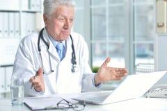 Doctor de sexo masculino mayor confiado con el estetoscopio que trabaja en oficina Imágenes de archivo libres de regalías
