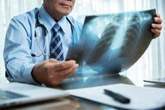 Doctor de sexo masculino mayor que mira a la película de radiografía Fotos de archivo libres de regalías