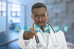 Doctor de sexo masculino negro africano enojado que señala el finger en usted con el estetoscopio Foto de archivo libre de regalías