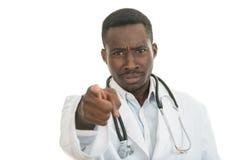 Doctor de sexo masculino negro africano enojado que señala el finger en usted con el estetoscopio alrededor de su cuello Imagen de archivo libre de regalías