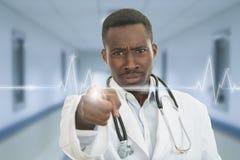 Doctor de sexo masculino negro africano enojado que señala el finger en usted con el estetoscopio alrededor de su cuello Imagen de archivo