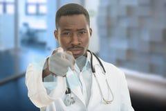 Doctor de sexo masculino negro africano enojado que señala el finger en usted con el estetoscopio alrededor de su cuello Imagenes de archivo