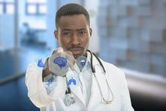 Doctor de sexo masculino negro africano enojado que señala el finger en usted con el estetoscopio alrededor de su cuello Fotos de archivo
