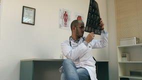 Doctor de sexo masculino que analiza imagen de la radiografía de la tomografía computada del cerebro almacen de video