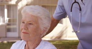 Doctor de sexo masculino que ayuda a la mujer mayor en la silla de ruedas en el patio trasero metrajes