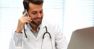 Doctor de sexo masculino que habla en el teléfono móvil mientras que trabaja en el ordenador almacen de metraje de vídeo