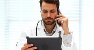 Doctor de sexo masculino que habla en el teléfono móvil mientras que usa la tableta digital almacen de metraje de vídeo