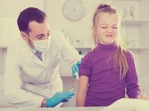 Doctor de sexo masculino que inyecta al pequeño paciente Imagen de archivo libre de regalías